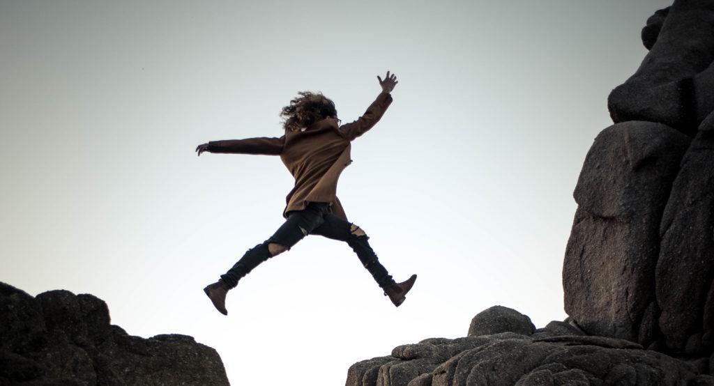 Eine Frau springt über eine Felsspalte